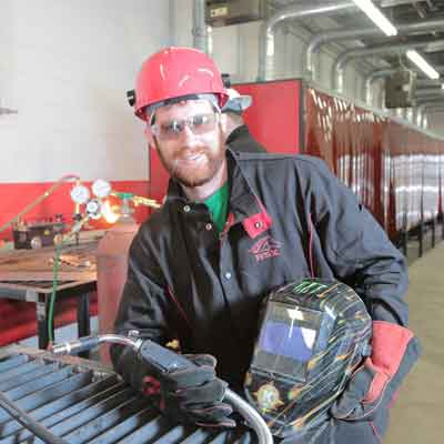 Welding student holding his equipment.