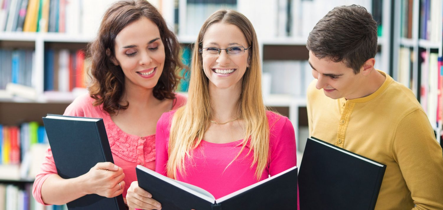Three students looking at a book together in the library.