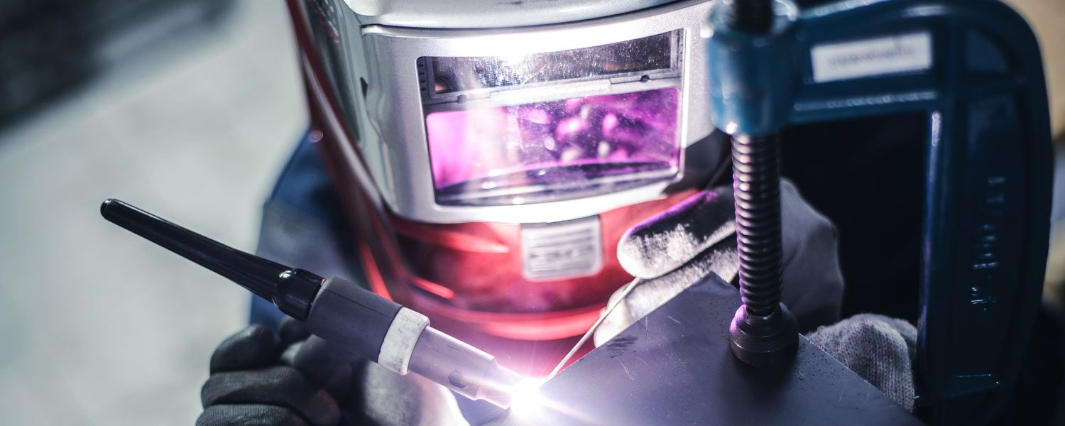 welder wearing welding helmet using a tig welding machine