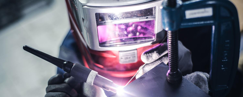 welder wearing welding helmet using a tig welding machine
